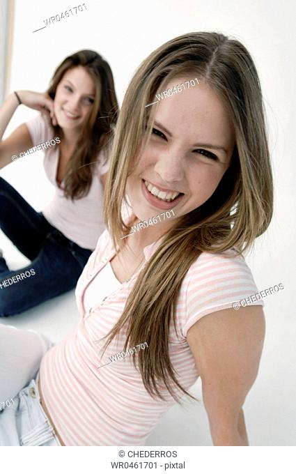 Portrait of a young woman making a face with another young woman smiling behind her