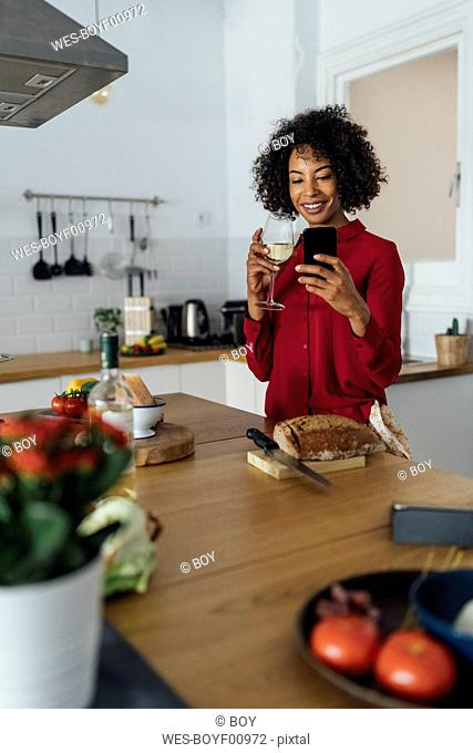 Woman drinking white wine in her kitchen, using smartphone