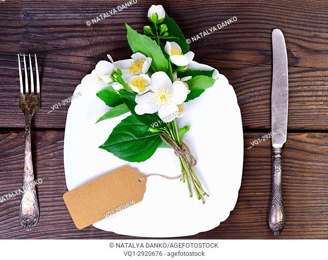square white plate and iron cutlery on a brown wooden background, top view