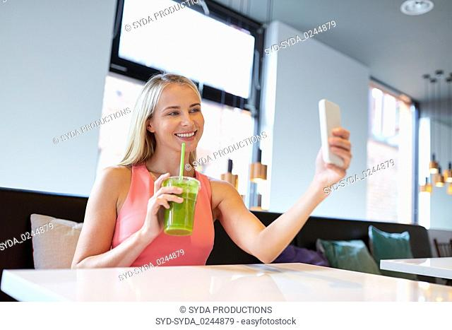 woman with smartphone taking selfie at restaurant