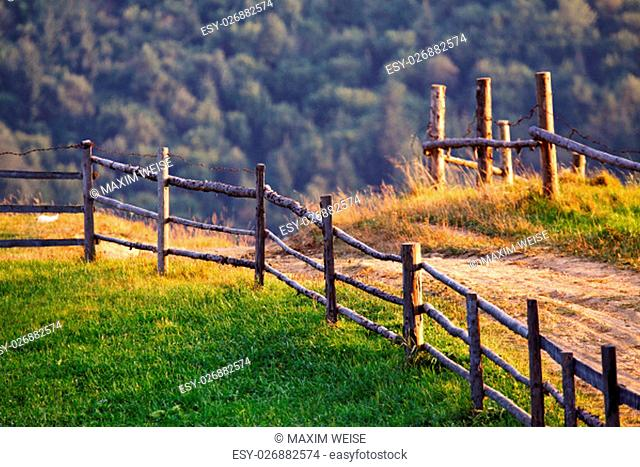 September rural scene in Carpathian mountains. Authentic village and fence