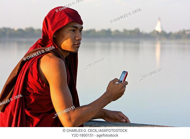 Myanmar, Burma, Mandalay  Buddhist Monk Taking Cell Phone Picture on the U Bein Bridge, Amarapura