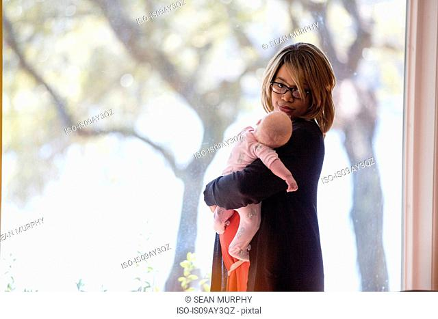 Young woman in front of window carrying baby daughter