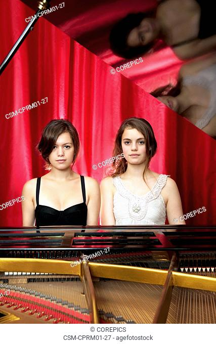 Two young woman playing together on a grand piano quatre mains