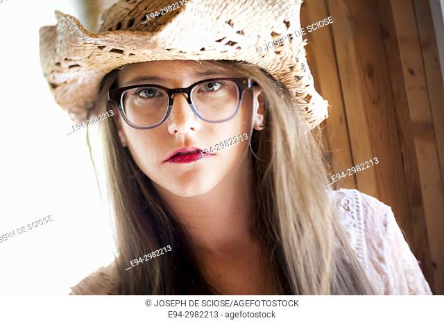 Portrait of a 26 year old woman with messy hair wearing a straw hat and large glasses looking at the camera