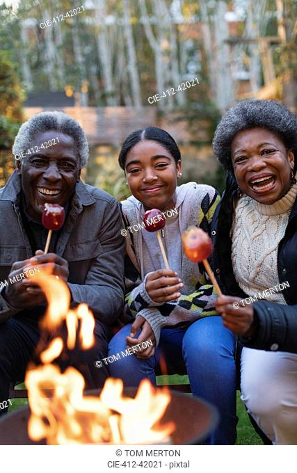 Portrait smiling, happy grandparents and granddaughter enjoying candy apples at campfire