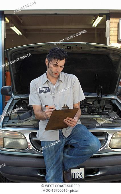 Mechanic writing on clipboard by open car hood