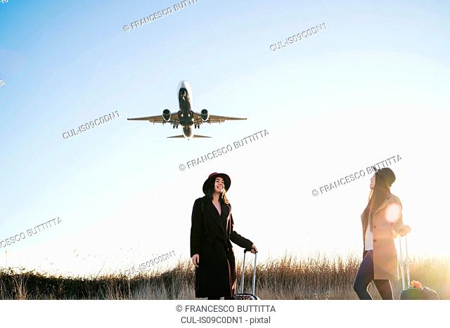 Friends waiting with wheeled luggage on roadside, airplane flying above