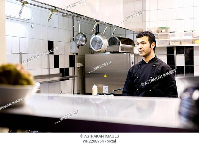 Male chef looking away while standing in commercial kitchen