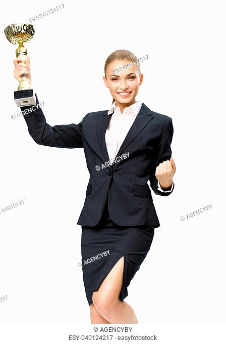 Businesswoman keeping golden cup and fist up gesturing, isolated on white. Concept of victory and success