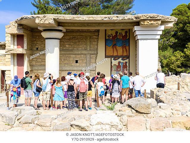 Knossos tour group viewing the Cup Bearer fresco at the South Propylaeum, Palace of Knossos, Heraklion, Crete, Greece
