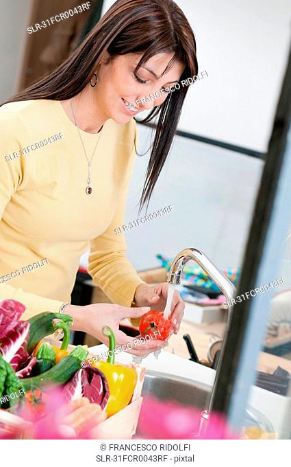 Woman washing tomato under fresh water