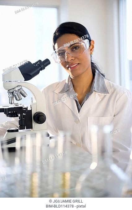 Indian scientist using microscope in lab