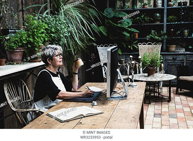 Senior woman wearing glasses, black top and white apron sitting at a wooden table, working on desktop computer