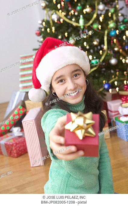 Portrait of girl in Santa hat in front of Christmas tree holding gift