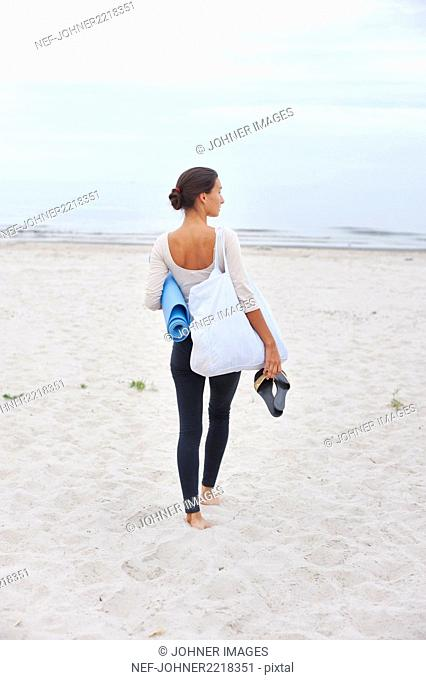Young woman with exercise mat standing on beach