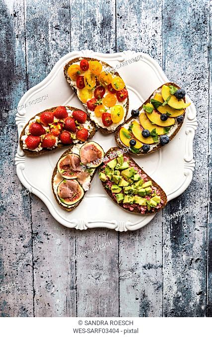 Various sandwiches, strawberry, fig, nectarine, avocado, tomato, on plate