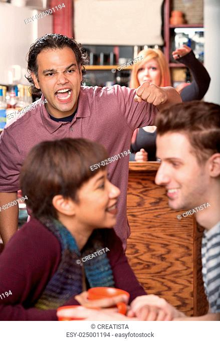 Hostile man with raised fist threatening loving couple in cafe