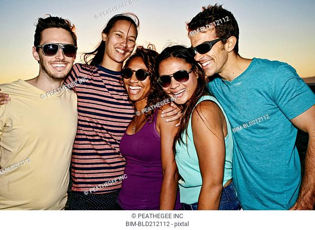 Friends smiling together on beach