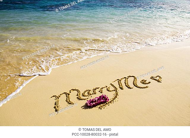 Turquoise ocean, foaming shore water, orchid lei, Marry Me written in sand