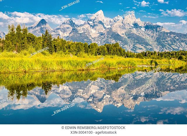 Teton Mountain Range and cloudy skies reflects on still waters of Snake River, Grand Tetons National Park, Teton County, Wyoming. USA