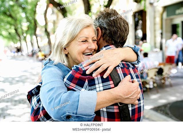 Happy senior couple embracing on the street