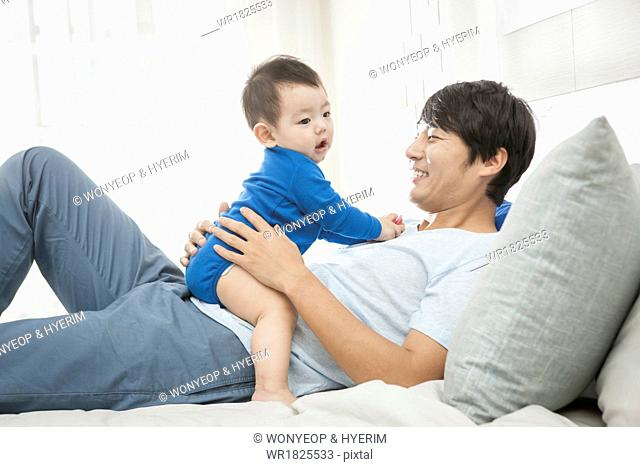 a father and a baby playing on the bed