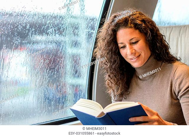 Young woman reading on a train as she commutes to work on a rainy day smiling as she enjoys a hardcover book