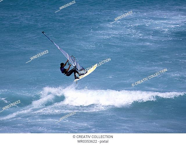 windsurfer doing acrobatics on a wave