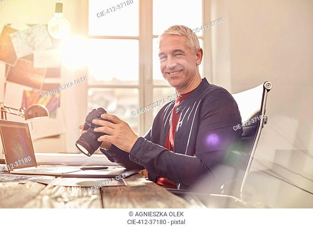Portrait smiling, confident male photographer with digital camera working at laptop in sunny office