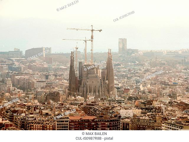 Elevated hazy cityscape view with La Sagrada Familia and construction cranes, Barcelona, Spain