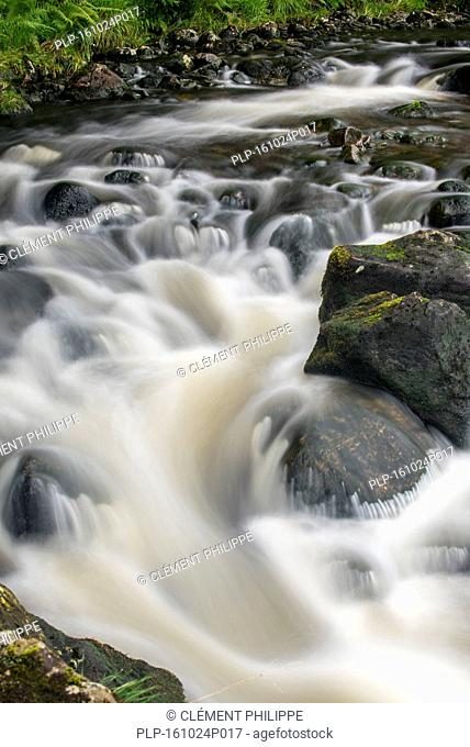 Detail of water flowing over boulders in the River Garry in Glengarry Forest, Lochaber, Scottish Highlands, Scotland