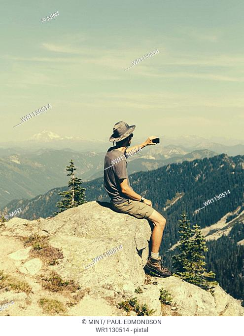 A hiker on a mountain summit, holding a smart phone, at the top of Surprise Mountain, in the Alpine Lakes Wilderness, in Mount Baker-Snoqualmie National Forest