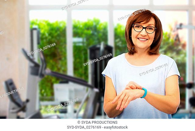 smiling senior woman with fitness tracker over gym