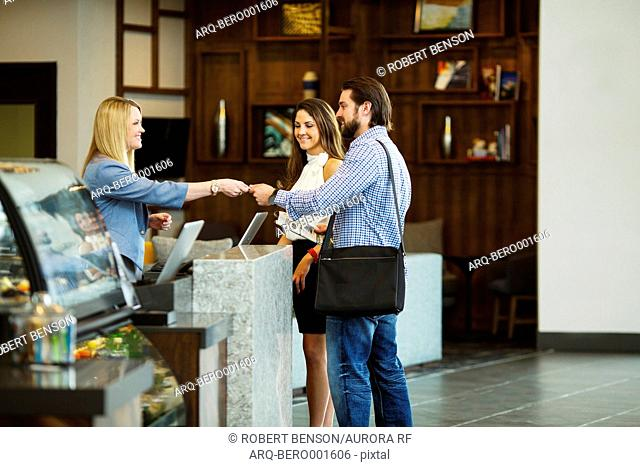 A nice looking couple takes their room key from receptionist at the reception