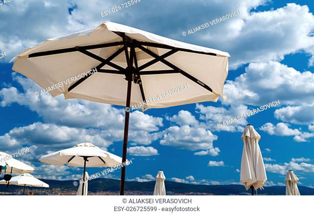 White beach umbrellas on a background of sea and sky. Shallow depth of field