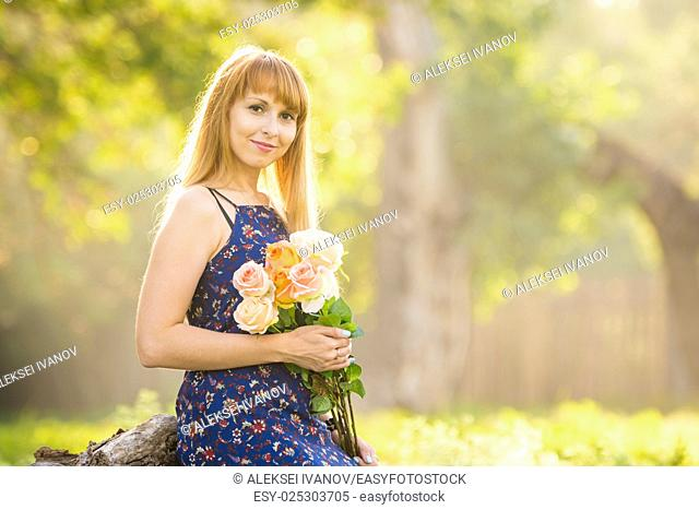 Beautiful young woman looking with a bouquet of roses in hands on a background of green sunny blurred