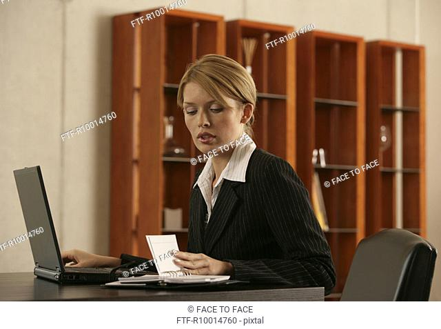 A blonde businesswoman looking at her appointment diary with a laptop beside her