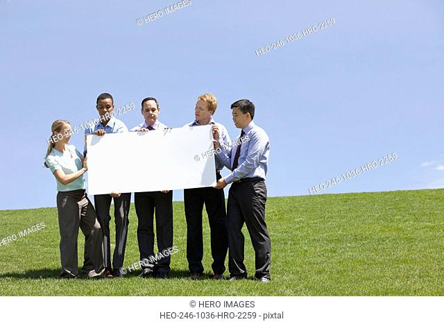 Group of business people displaying blank sign together