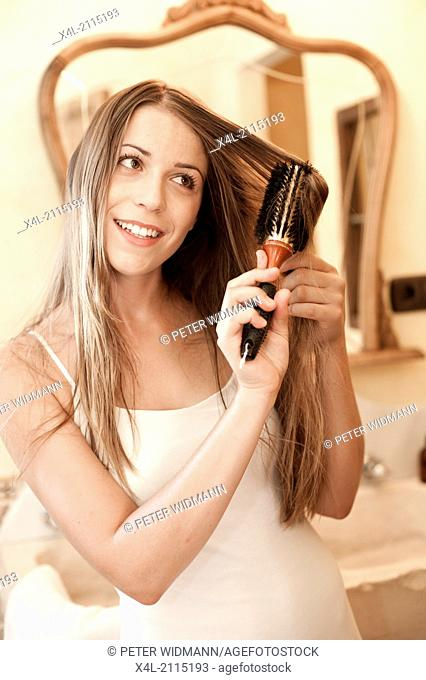 young, pretty woman in bathroom doing her hair (model-released)
