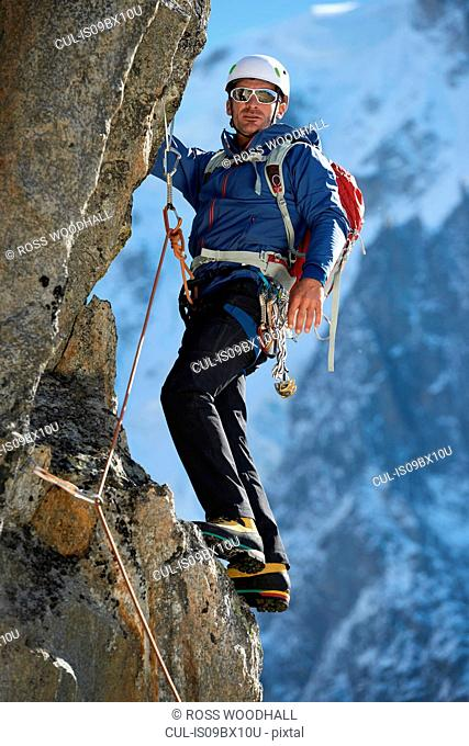 Mountaineer using harness for climb, Chamonix, Rhone-Alps, France