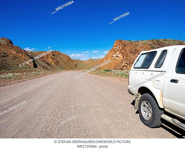 Namibia, Kunene, car on an unpaved road in a hilly landscape, on the journey from Khorixas to Palmwag