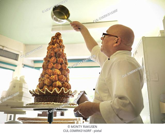 Baker pouring sugar over decorated cake