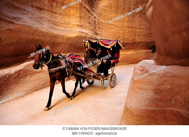 Coach with tourists in the Siq, the one kilometer long canyon that leads to the Nabataean city Petra, Unesco World Heritage Site, near Wadi Musa, Jordan
