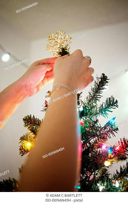 Woman putting star on Christmas tree