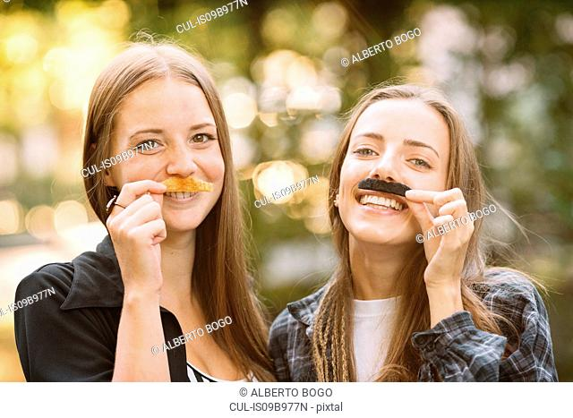 Portrait of two young female friends holding false moustache to their face in park