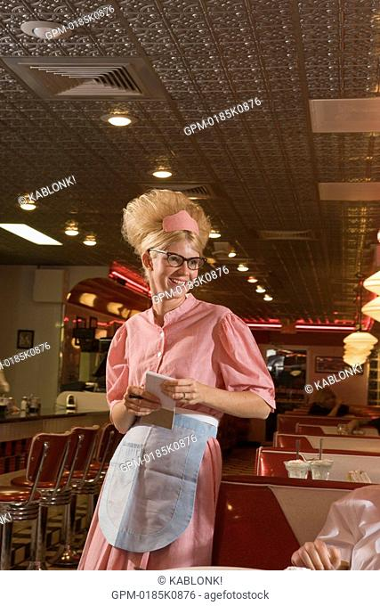 Young waitress in 1950s style uniform taking order at old-fashioned diner