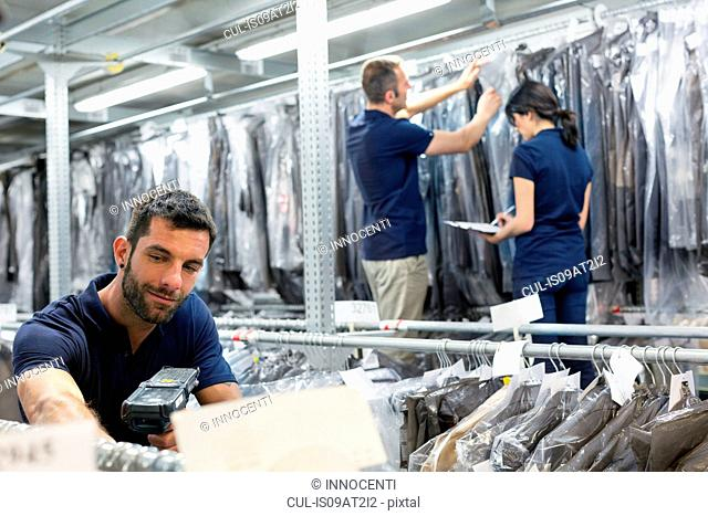 Three warehouse workers preparing garments in distribution warehouse