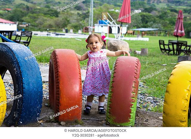 Baby girl playing in a play ground full of colorful tires