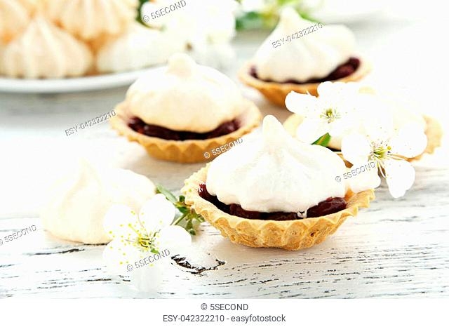 French meringue cookies in tartlet on white wooden background
